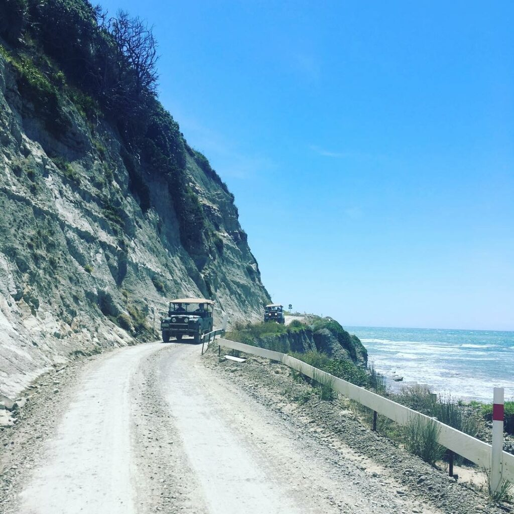 Land Rovers convoy on road to east cape lighthouse. narrow road beside sea. #nzmvc #landrover New Zealand Military Vehicle Club Inc